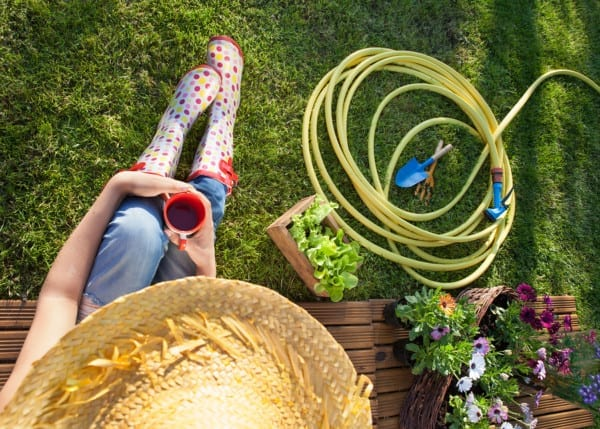 Woman having a coffee break while working in the garden, spring gardening concept